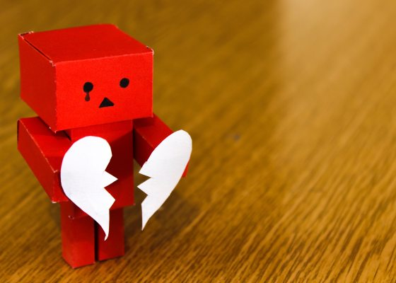 Paper robot holding broken heart