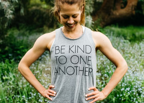 Woman with hands on hips and shirt that says be kind to one another