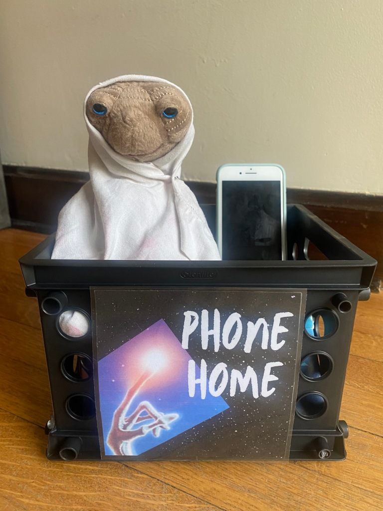 E.T. in basket with phone. Sign saying Phone Home.